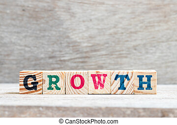 Letter block in word growth on wood background