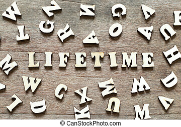 Letter block in word lifetime with another alphabet on wood background