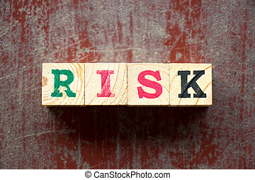 Letter block in word risk on old red wood background