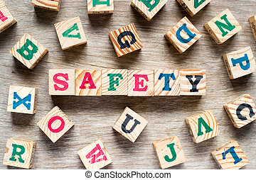 Letter block in word safety with another alphabet on wood background
