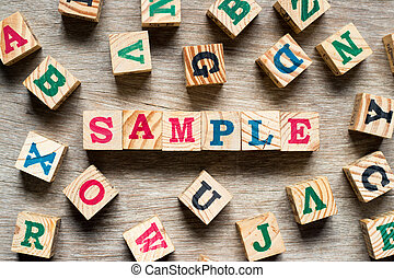 Letter block in word sample with another alphabet on wood background