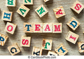 Letter block in word team with another on wood background
