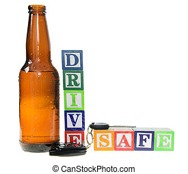 Letter blocks spelling drive safe with a beer bottle and keys