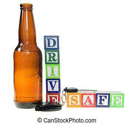 Letter blocks spelling drive safe with a beer bottle and keys