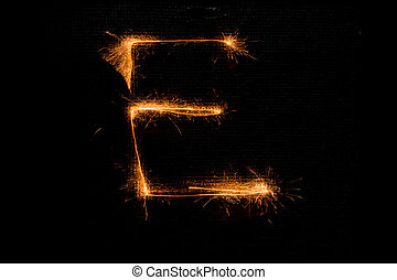 Letter E made of sparklers on black