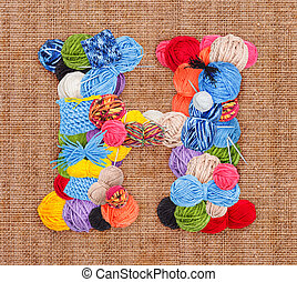Letter H made of knitting yarn on burlap background