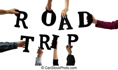 Hands holding up the letters to spell out the word ROAD TRIP.