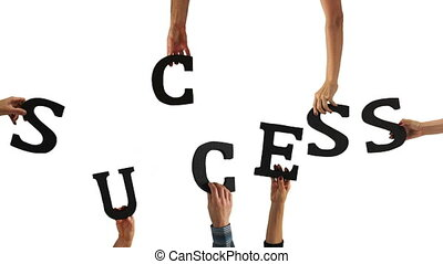 A bunch of people's hands holding the letters that spell out the word SUCCESS to signify a team of people working together to achieve their goal.