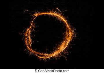 Letter O made of sparklers on black