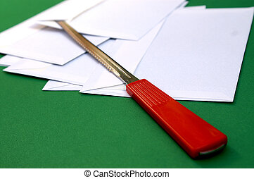 Contrsting brightly coloured red letter opener on green desk with envelopes