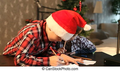 Letter to Santa - Two boys writing a letter to Santa Claus