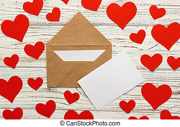 Letter to Valentine Day. Love letter envelope with red hearts on wooden background
