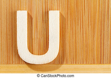 Letter U of wood-made alphabet, top view and space for text