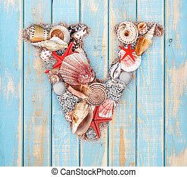Letter V made of seashell on blue wooden background