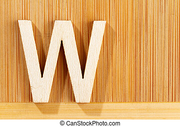 Letter W of wood-made alphabet, top view and space for text