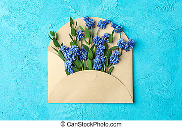 Letter with fresh hyacinths on blue background, top view