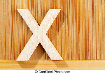 Letter X of wood-made alphabet, top view and space for text