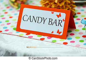Lettering 'candy bar' stands on a table in restaurant