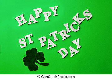 Lettering Happy St. Patrick's day, laid out on green background.