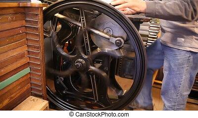 a printer operates a manual letterpress