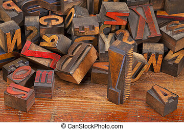 a variety of vintage wooden letterpress printing blocks, stained by color inks, placed randomly on an old wood surface, focus on exclamation point