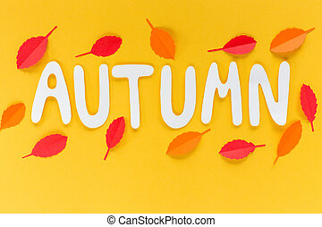 letters autumn on an orange background with leaves