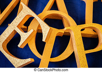 letters cut out of polystyrene with gold color on a blue ...