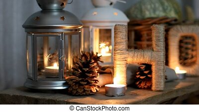 Letters drawn up in the form of the word HOME with pumpkins, pine cones by candlelight