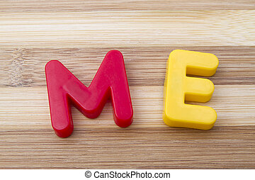 "Letters magnets "" ME"" closeup on wood background"