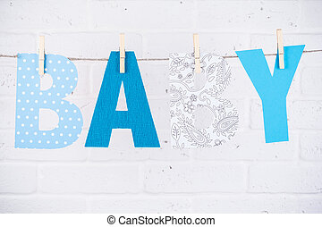 letters of word baby hanging on clothesline against white brick