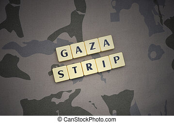 letters with text gaza strip on the khaki background. ...