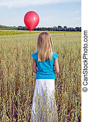 Letting Go - Young girl releasing red balloon in wheat field...