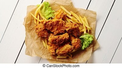 Lettuce and French fries near chicken wings - From above...