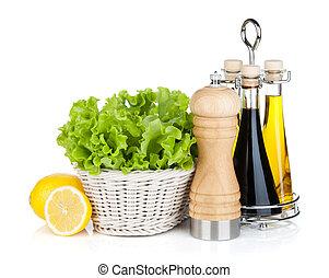 Lettuce in basket with lemon fruits, pepper shaker, olive ...