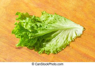 Lettuce leaf on the wooden cutting board
