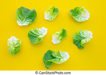 Lettuce leaves on yellow background. Top view