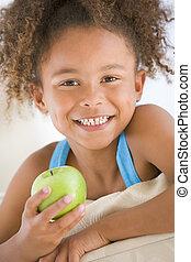 levande, ätande äpple, ung, leende flicka, rum