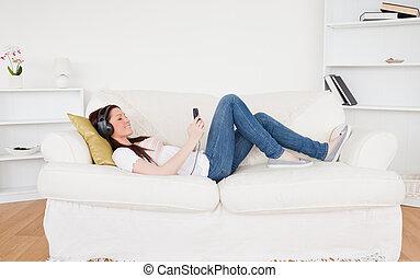 levande, lyssnande, rödhårigt, soffa, hörlurar, medan, musik, attraktiv, kvinnlig, lögnaktig, rum
