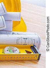 level rolls of blueprints and helmet on wooden boards constructi