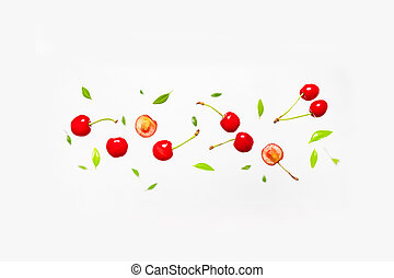 Falling cherries with green leaves on grey background.