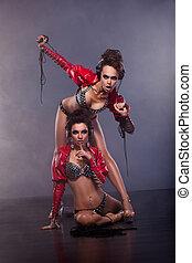 Lewdness. Two Flirty Woman in Erotic Pose Enjoying Music....