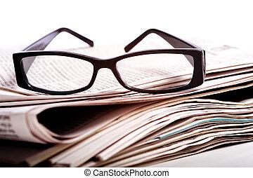 lezende glazen, op, kranten