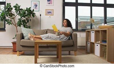 lezende , jonge vrouw , boek, vrolijke , sofa, thuis