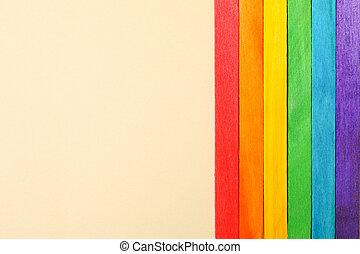 LGBT flag made of wooden sticks on beige background