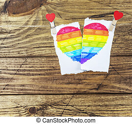 Torn and folded drawn heart with LGBT rainbow on clothespins with hearts on a wooden background