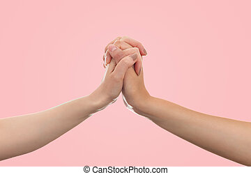 LGBT. Two females hands are holding each other. Copy space. Pink background. Concept of the LGBT movement and gay day