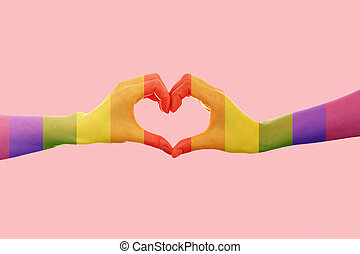 LGBT. Two females hands, painted in the colors of the rainbow flag, show the heart sign with their fingers. Pink background. Copy space. The concept of the LGBT movement and gay day