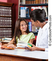Librarian And Schoolgirl Looking At Each Other In Library -...