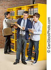 Librarian And Student Reading Book In Library