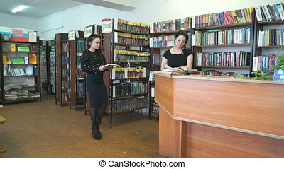 Librarian helps to find books for young woman - Attractive...